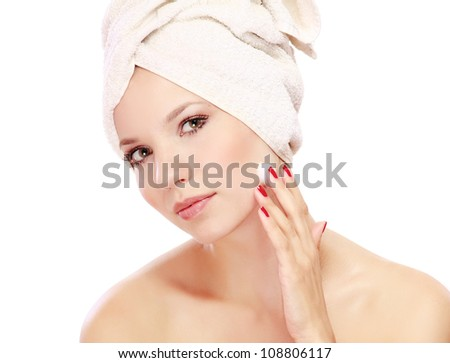 Young beautiful woman applying cream on her face - stock photo