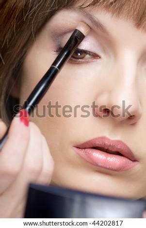 Young beautiful woman applying eye shadow, closeup - stock photo