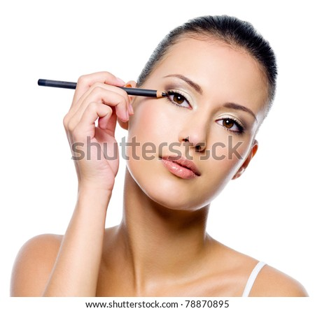 Young beautiful woman applying eyeliner on eyelid with brush - isolated - stock photo