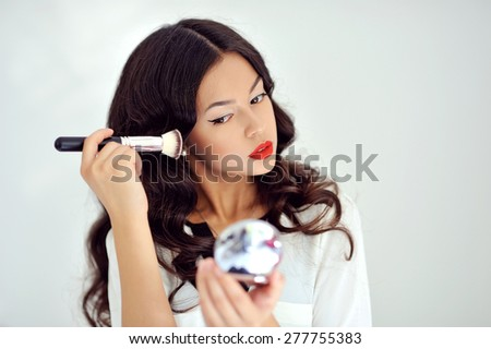 Young beautiful woman applying her make up, looking in a mirror - stock photo
