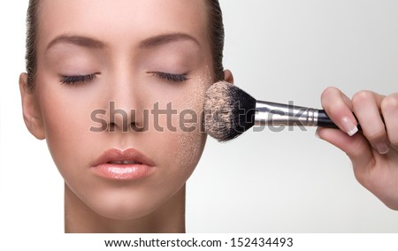 Young beautiful woman applying make-up powder on the cheek. Studio shot on neutral background. - stock photo