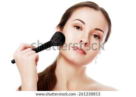 Young beautiful woman applying makeup on face by brush - stock photo