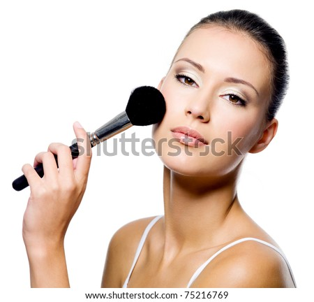 young beautiful woman applying powder on cheek with brush - isolated - stock photo