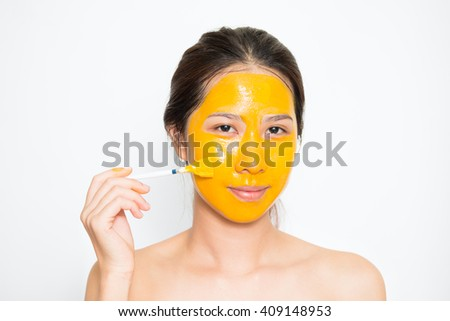 Young beautiful woman applying yogurt and turmeric facial mask Skin care, beauty treatments on white background - stock photo