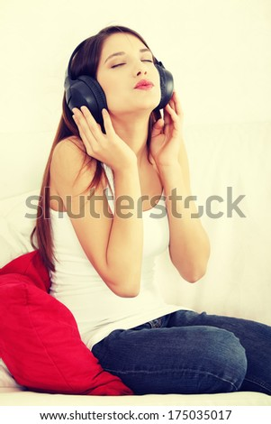 Young beautiful woman at home sitting on sofa and listening music  - stock photo