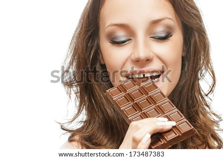 Young beautiful woman bites off slice from chocolate bar, on white background. - stock photo
