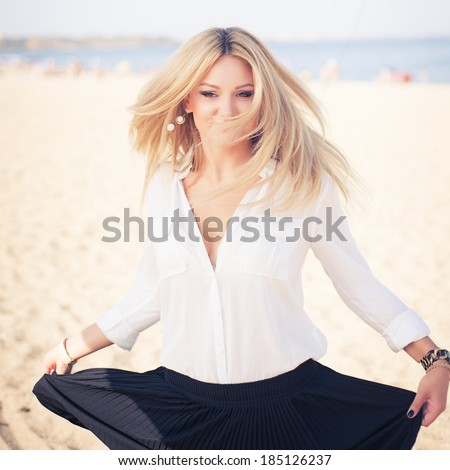 young beautiful woman blonde poses on a beach. dressed in a white shirt and a black skirt. fashion model. dancing. Photo in color style instagram filters  - stock photo
