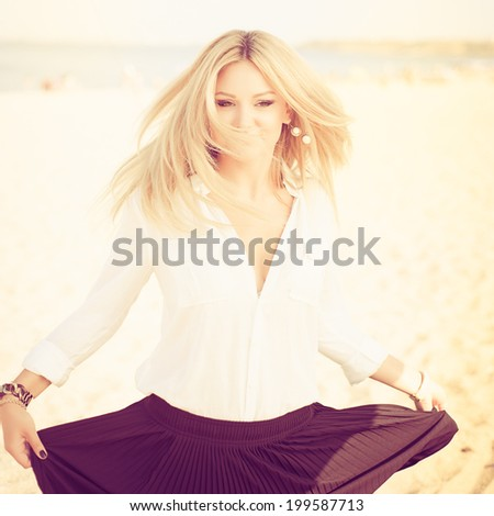 young beautiful woman blonde poses on a beach. dressed in a white shirt and a black skirt. fashion model. dancing. Photo with instagram style filters - stock photo