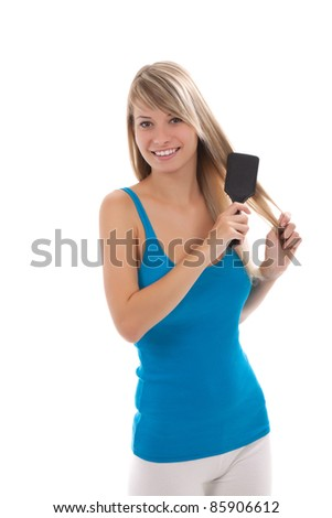 Young beautiful woman combing hair and looking at camera, isolated over white background - stock photo