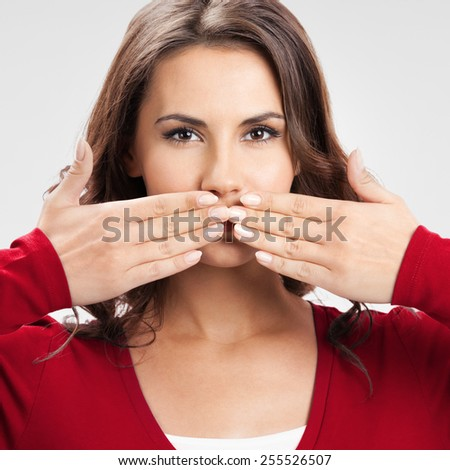 Young beautiful woman covering with hands her mouth, over grey background - stock photo
