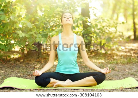 Young beautiful woman doing yoga exercises in park - stock photo