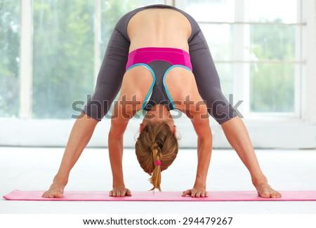 Young beautiful woman doing yoga indoors. - stock photo