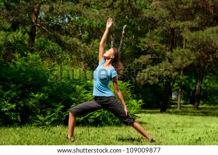 Young beautiful woman doing yoga meditation exercise outdoors - stock photo