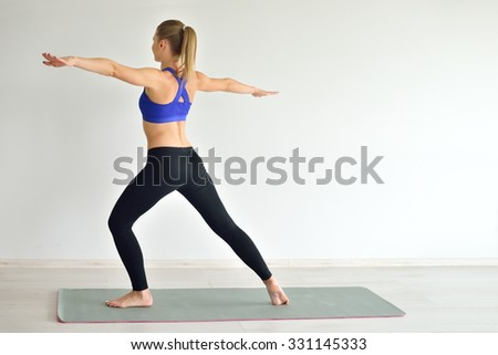 Young beautiful woman doing yoga poses indoor on grey background. Girl practicing her body in gym. - stock photo