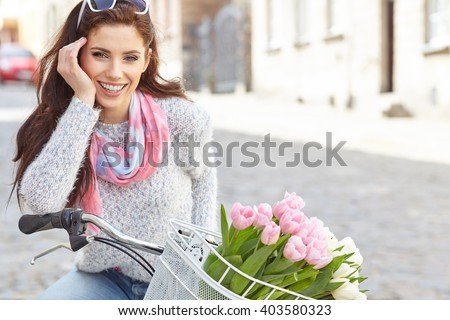 Young beautiful woman dressed in pastel on bicycle, pink and white tulips in a basket, spring outdoor. - stock photo