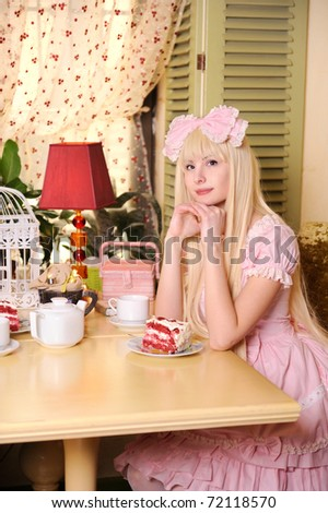Young beautiful woman dressed in pink lace dress with cake. - stock photo