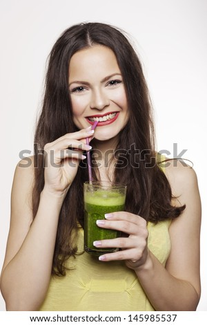 Young beautiful woman drinking a healthy raw fruit vegetable juice. Studio shot  - stock photo