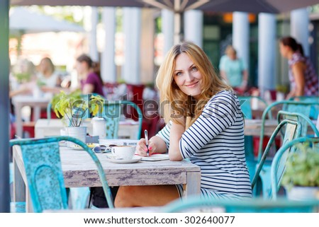 Young beautiful woman drinking coffee and writing diary, book or notes in an outdoor cafe in London, United Kingdom. - stock photo