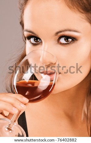 Young beautiful woman drinks wine from wine glass, close up. - stock photo