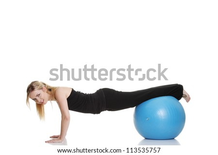 Young beautiful woman during fitness time and exercising with blue ball, isolated on white background - stock photo