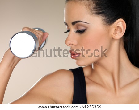 Young beautiful woman during fitness time with dumbbells - stock photo