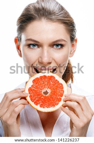 Young beautiful woman eat grapefruit / good looking girl of the european appearance biting a cut piece of grapefruit - isolated on white background  - stock photo