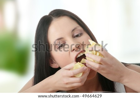 Young beautiful woman eating chips - stock photo