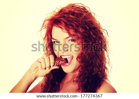 Young beautiful woman eating chocolate bar, isolated on white - stock photo
