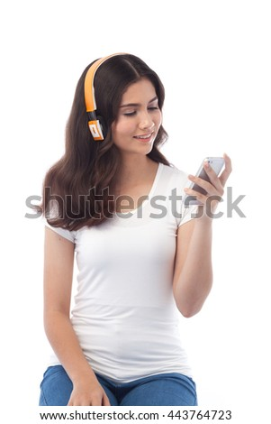 Young beautiful woman enjoy music with smartphone and bluetooth wireless headphone. Isolated white background, white t-shirt. - stock photo