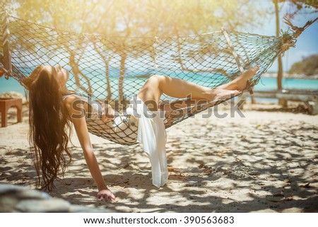 Young beautiful woman enjoying and relaxing in  hammock on tropical sea shore. Exotic paradise - stock photo
