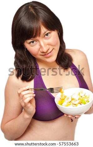 young beautiful woman enjoying fruit salad - stock photo