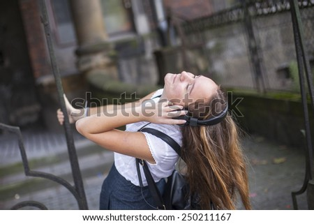 Young beautiful woman enjoying music on headphones on the street. - stock photo