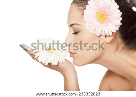 young beautiful woman enjoying the scent of the flower gerbera - stock photo