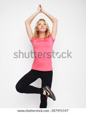 young beautiful woman exercising yoga with her arms over her head on white background - stock photo