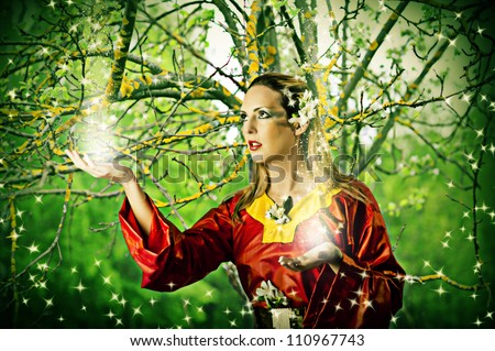 Young beautiful woman fairy in summer magic forest - stock photo