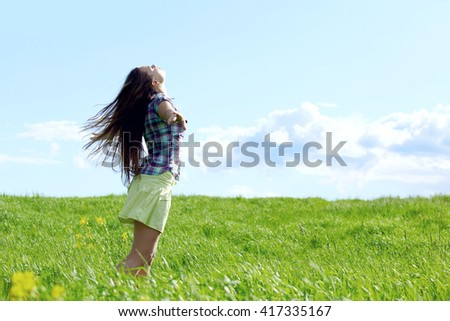 Young beautiful woman feeling freedom on meadow - stock photo