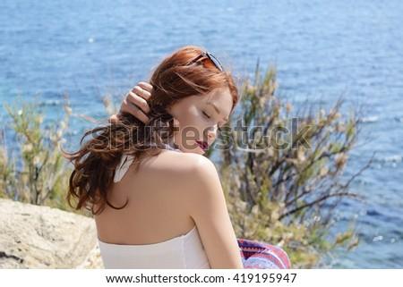 Young beautiful woman feeling the sea breeze - stock photo