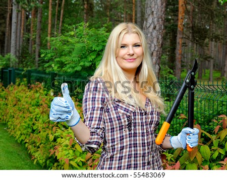 Young beautiful woman gardening and trimming the hedge - stock photo