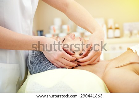 young beautiful woman getting facial massage and relaxing - stock photo
