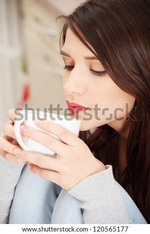 Young beautiful woman having coffee or tea in the kitchen - stock photo