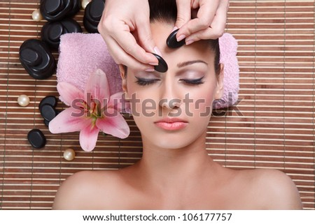 young beautiful woman having facial massage with mineral stone - stock photo