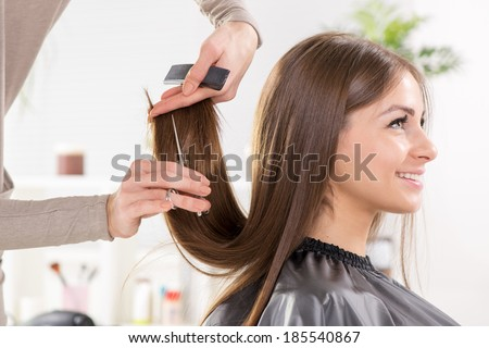 Young beautiful woman having her hair cut at the hairdresser's. - stock photo