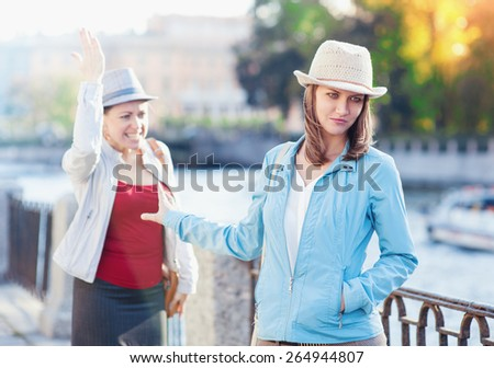 Young beautiful woman having quarrel with her friend in the city outdoor - stock photo
