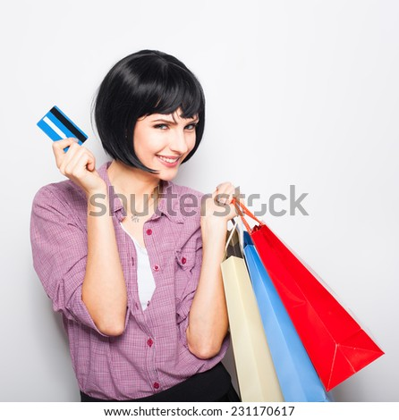 young beautiful woman having shopping colored bags over shoulder and credit card in hand - stock photo