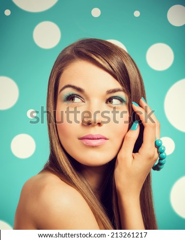 Young beautiful woman holding a turquoise bracelet with bright color manicure and makeup. Girl looking to the side. Vintage styled colors.  - stock photo