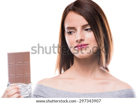 Young beautiful woman holding bar of chocolate and looking on it, white background. - stock photo