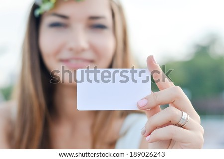 Young beautiful woman holding blank business card with copy space  - stock photo