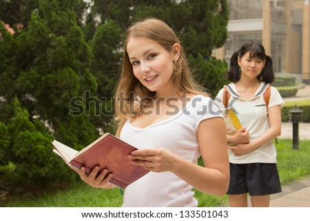 Young beautiful woman holding book at city park. Group of student girls in the university campus - stock photo