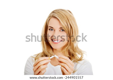 Young beautiful woman holding broken cigarette in front. - stock photo