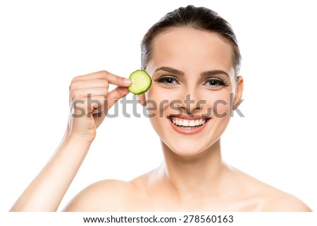 Young beautiful woman holding cucumber slices on the face. White background. - stock photo